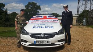 Two military reservists in military uniform by a Police car
