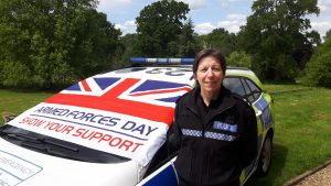 Insp Sewell in uniform by a Police car