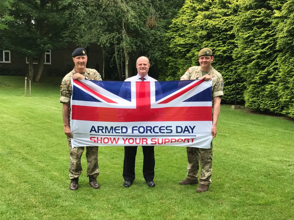 Reservist, Veteran and Cadet Instructor holding Armed Forces Day flag