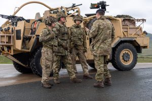 Unit member being briefed next to a Jackal 2 vehicle