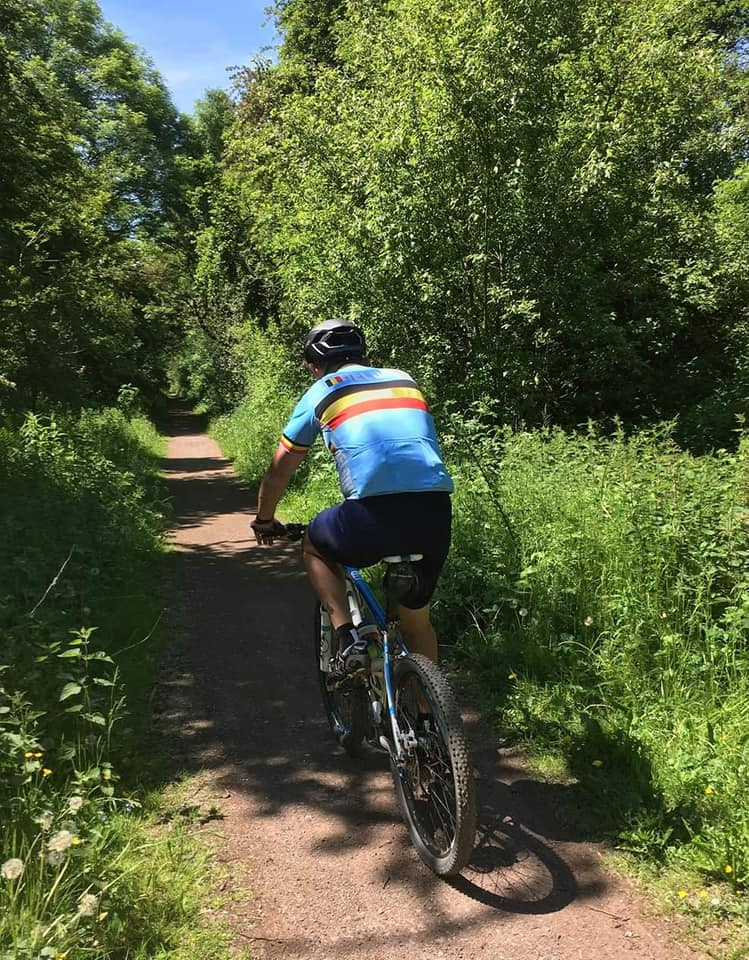 A member of 605 Squadron RAF Reserves passes through a scenic trail on his bike, surrounded by grass and trees as part of the challenge