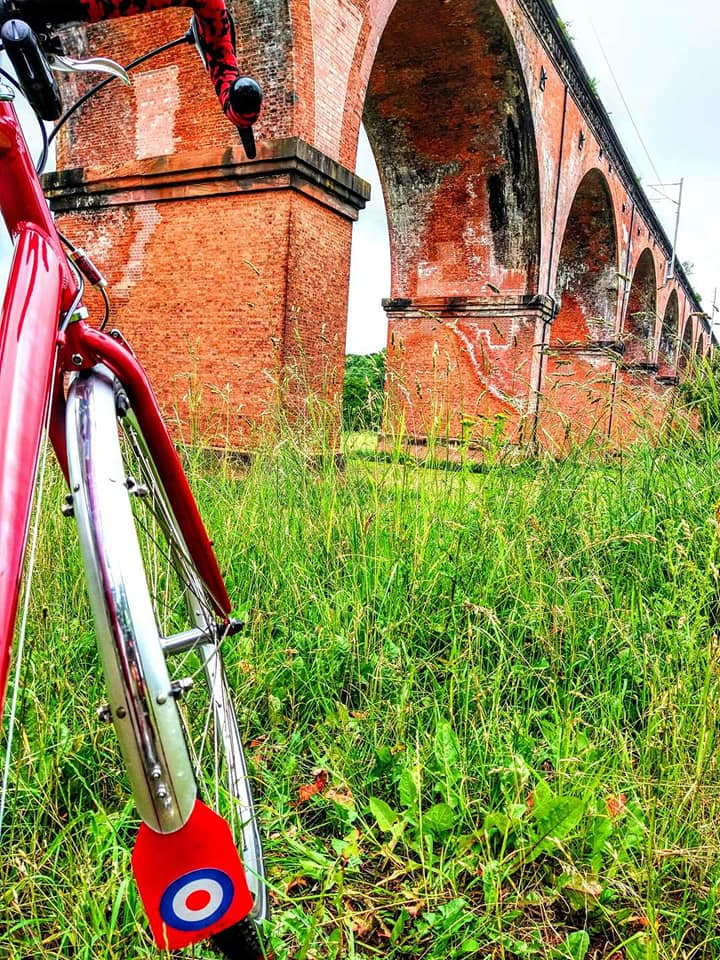 The front wheel of a bike displaying a Royal Air Force logo is propped up in front of an aquaduct