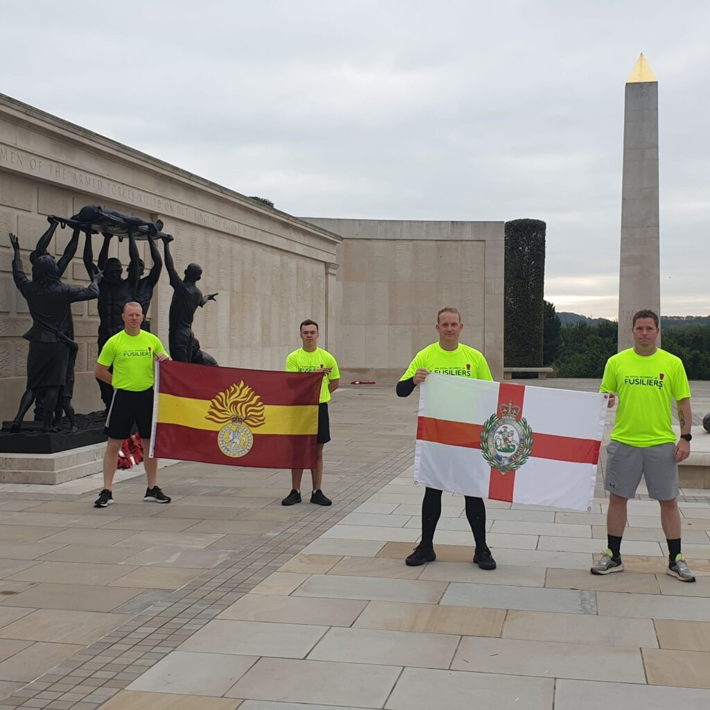 The 'Running Fusiliers' team pose with their regiment's flags at the National Memorial Arboretum, which was one of the landmarks they passed through on their 300 mile run
